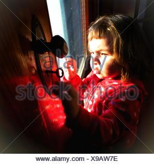 Niedliche Mädchen öffnende Tür mit Schlüssel zu Hause - Stockfoto