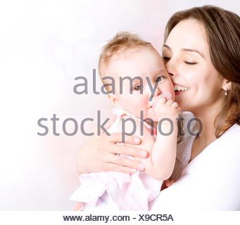 Mutter und Baby küssen und umarmen. Glückliche Familie - Stockfoto