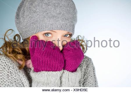 Eine junge Frau mit Hut und Handschuhen, versucht warm zu halten - Stockfoto
