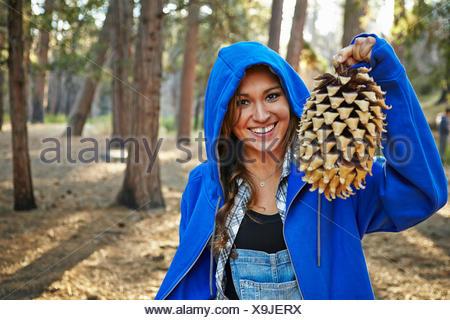 Porträt der jungen Frau im Wald hält große Tannenzapfen, Los Angeles, Kalifornien, USA - Stockfoto