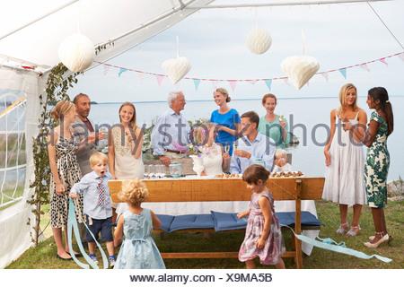 Mitte erwachsenes paar Hochzeitsfeier mit großen Gruppe von Freunden zu genießen