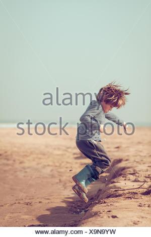 Junge springt in den Sand am Strand, Marokko - Stockfoto