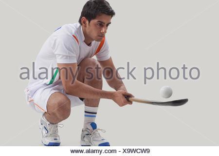 Junger Mann üben Hockey auf grauem Hintergrund isoliert - Stockfoto