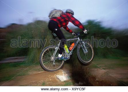 Ein Mountainbiker auf ein Singletrack Trail über eine Lücke springen - Stockfoto