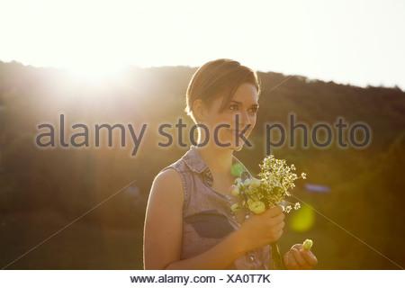 Junge Frau in Wiese mit wilden Blumen - Stockfoto