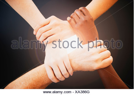 Vier Hände halten Handgelenke anderer Menschen - Stockfoto