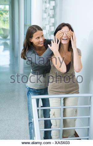 Teen Mädchen steht hinter Mutter, übergibt ihre Augen, beide Lächeln, drei Viertel Länge - Stockfoto