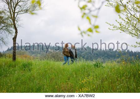 Reife Frau und Tochter im Teenageralter auf Feldern spazieren - Stockfoto