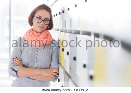 Porträt von zuversichtlich Geschäftsfrau stehend Arme gekreuzt in Umkleidekabine in Kreativbüro - Stockfoto