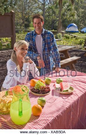 Mid-Adult paar an Picknick-Tisch in der Nähe von Campingplatz - Stockfoto