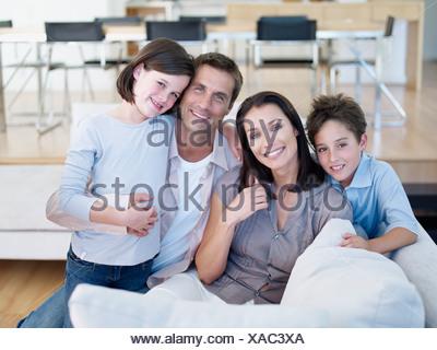 Mann und Frau mit jungen und Mädchen sitzen auf dem sofa - Stockfoto