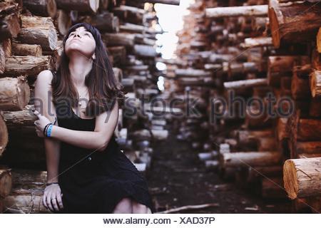 Frau sitzt im Wald auf der Suche, Arme im Freien halten
