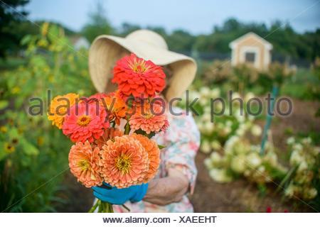 Ältere Frau mit Blumen vor Gesicht auf Bauernhof - Stockfoto