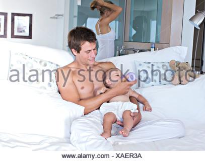 Vater Fütterung sein Baby, Mutter im Hintergrund, im Innenbereich - Stockfoto