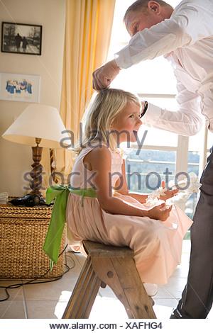 Vater bereitet Mädchen an den Haaren - Stockfoto