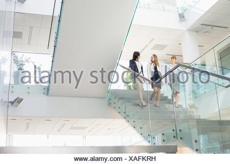 Unternehmerinnen im Gespräch während der Bewegung nach unten Schritte im Büro - Stockfoto