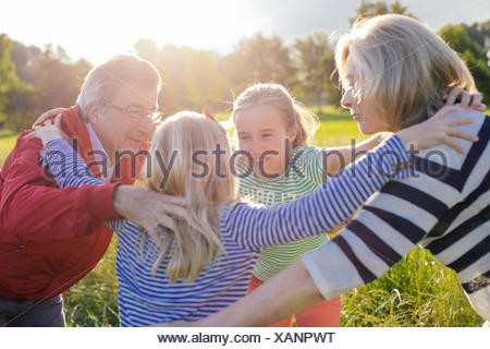 Großeltern und Enkelinnen im huddle - Stockfoto
