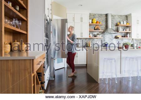 Frau, die Kühlschranktür zu öffnen, in der Küche - Stockfoto