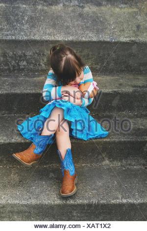 Mädchen sitzen auf einem Schritt umarmt eine Babypuppe