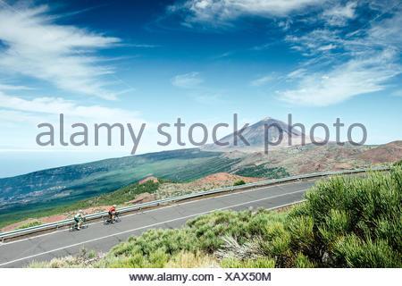 Zwei Radfahrer radeln auf Mountain Road mit Teide im Hintergrund Mount, Nationalpark Teide, Teneriffa, Kanarische Inseln, Spanien - Stockfoto