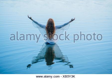 Rückansicht des jungen Frau im blauen See mit offenen Armen