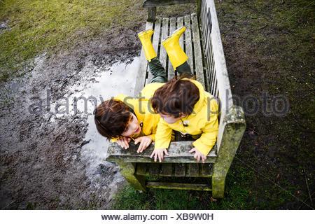 Draufsicht der Baby und Bruder in gelben Anoraks auf Parkbank - Stockfoto