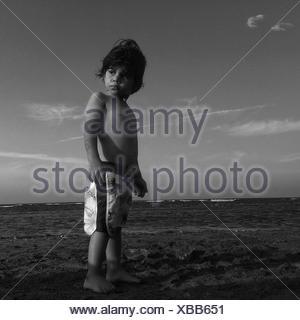 Niedrigen Winkel Blick auf nacktem Oberkörper Boy wegschauen im stehen am Strand - Stockfoto