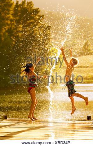 Jungen und Mädchen in Luft auf Steg durch Spritzer Wasser springen - Stockfoto