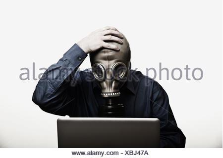 Studioaufnahme des Mannes vor Laptop mit Gasmaske - Stockfoto
