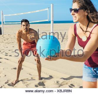 Gruppe von Freunden, die am Strand Volleyball spielen