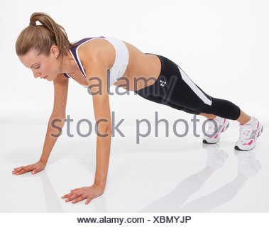 Oberkörper trainieren weibliche blondes Haar gebunden zu Pferdeschwanz tragen eine kurze Weste, schwarze Leggings und Trainer, Durchführung einer - Stockfoto