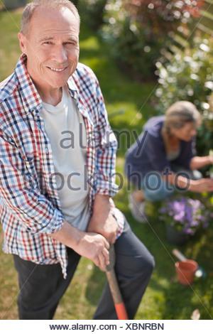 Porträt von lächelnden senior Mann arbeitet im sonnigen Garten - Stockfoto