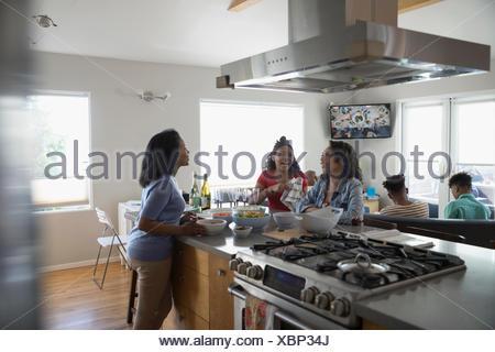 African American Mutter und Töchter im Teenageralter Kochen und Essen in der Küche - Stockfoto