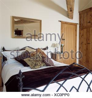 Land-Schlafzimmer mit Spiegel an der Wand über Gothic-Stil Bett mit ...