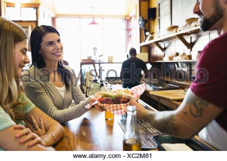 Männliche Deli Besitzer Speisen an Kunden am Schalter - Stockfoto