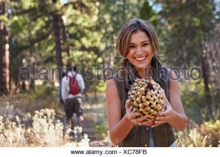 Porträt der jungen Frau im Wald mit großer Tannenzapfen, Los Angeles, Kalifornien, USA - Stockfoto