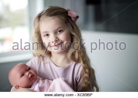 Porträt eines Mädchens mit Babypuppe in Handtuch gewickelt. Kind, Glück, Spielzeug, Kinderbetreuung.