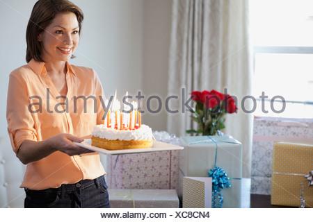 Lächelnde Frau hält Geburtstagstorte zu Hause - Stockfoto