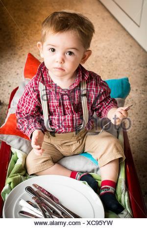 Baby Boy, 18 Monate alt, hilft mit dem Geschirr. - Stockfoto
