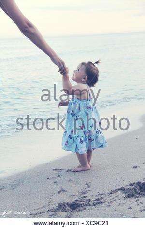 Babymädchen hielt ihre Mutter seiner Hand am Strand - Stockfoto