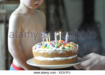 Junge Ausblasen der Kerzen auf der Geburtstagstorte - Stockfoto