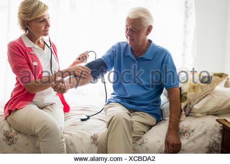 Krankenschwester kümmert sich um einen älteren Mann - Stockfoto