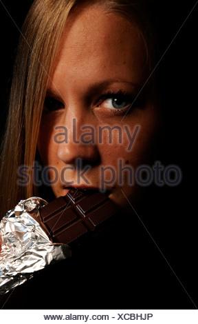 Eine junge Blonde Frau einen Schokoriegel essen - Stockfoto