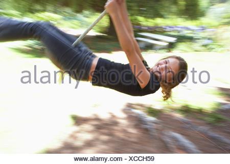 Mädchen 9 11 schwingen am Seil in Garten lächelnd Seitenansicht Bewegung verwischt - Stockfoto