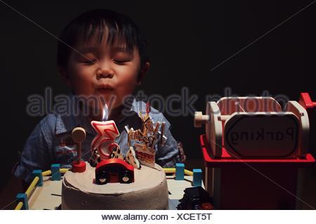 Süsser Boy mit Auge geschlossen bläst Geburtstag Kerze auf Kuchen In Dunkelkammer - Stockfoto