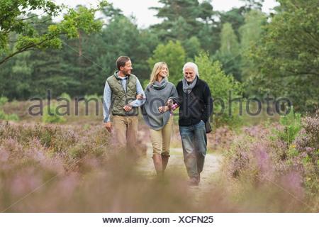 Ältere Mann Mitte erwachsenen Mann und Frau zu Fuß durch Wald - Stockfoto