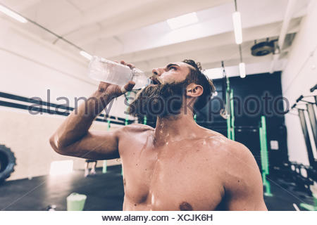Erschöpft von Trinkwasser männliche Cross-Trainer im Fitness-Studio - Stockfoto