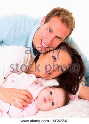 Baby Mädchen Mutter und Vater Familie glücklich zusammen auf weißem Fell liegend - Stockfoto