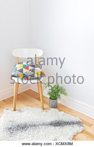 Stuhl mit hellen Kissen und Schaffell Teppich auf dem Boden - Stockfoto