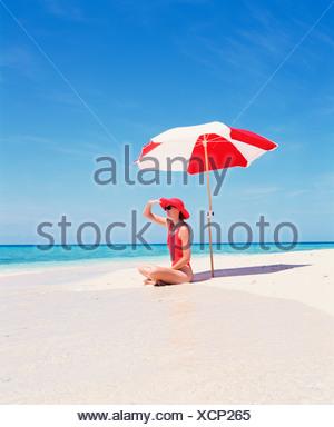 Junge Frau im roten Badeanzug sitzt unter Sonnenschirm alleine an einem verlassenen Strand. - Stockfoto